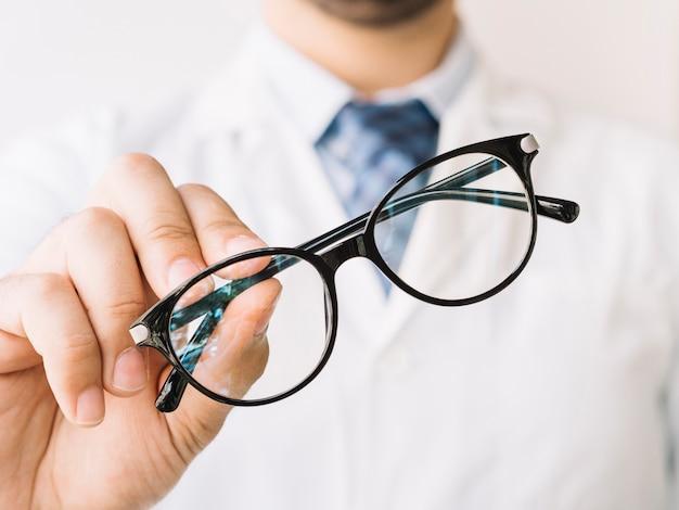 Доктор, держащий очки в черной оправе Бесплатные Фотографии