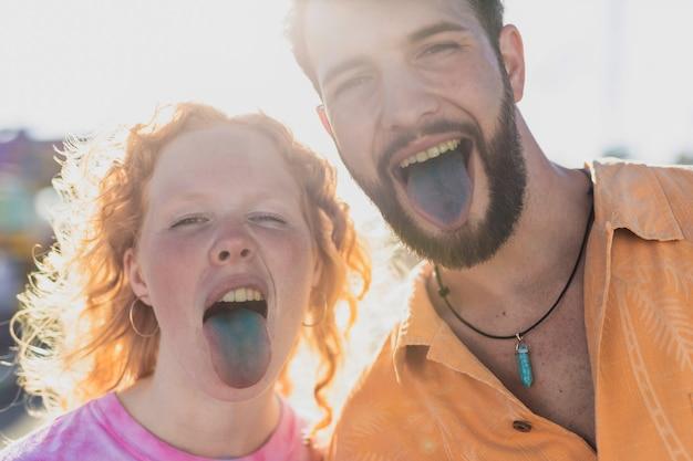 Крупным планом счастливая пара с синими языками Бесплатные Фотографии