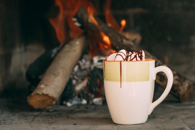 暖炉のそばのマグカップとの配置 無料写真