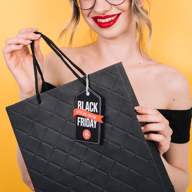 黒い金曜日のデザインとバッグを保持しているクローズアップの女性 無料写真