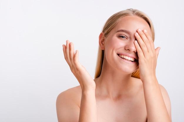 片手で彼女の目を覆っているクローズアップスマイリー女性 無料写真