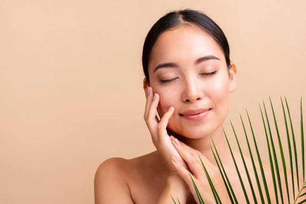 Азиатская женщина крупным планом с листьями Бесплатные Фотографии