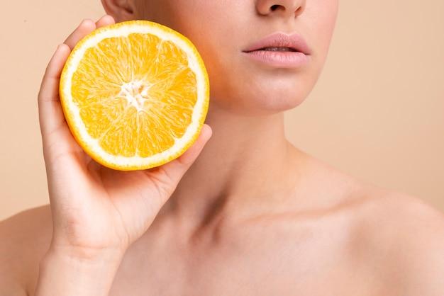 ハーフオレンジとクローズアップの美しいモデル 無料写真