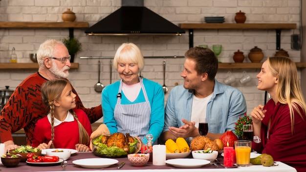 感謝祭のディナーテーブルに座っている家族の世代 無料写真