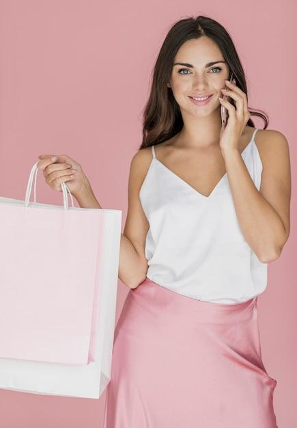 ショッピングネットとスマートフォンのきれいな女性 無料写真