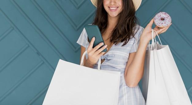 灰色のスマートフォンと縞模様のドレスの甘い女性 無料写真
