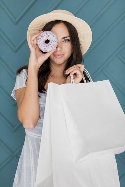 Дама с хозяйственными сумками закрыла глаза пончиком Бесплатные Фотографии