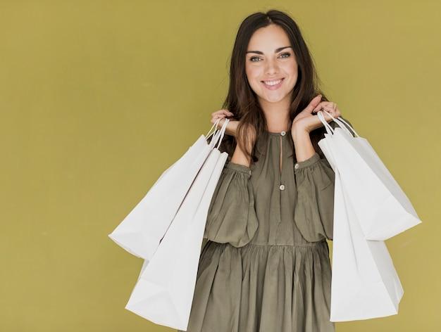 Женщина с покупками сетей в обе руки, улыбаясь в камеру Бесплатные Фотографии