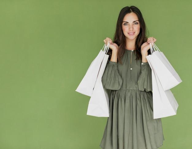 Женщина с сумками в обеих руках на зеленом фоне Бесплатные Фотографии