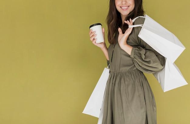 コーヒーとショッピングネットのドレスで陽気な女性 無料写真