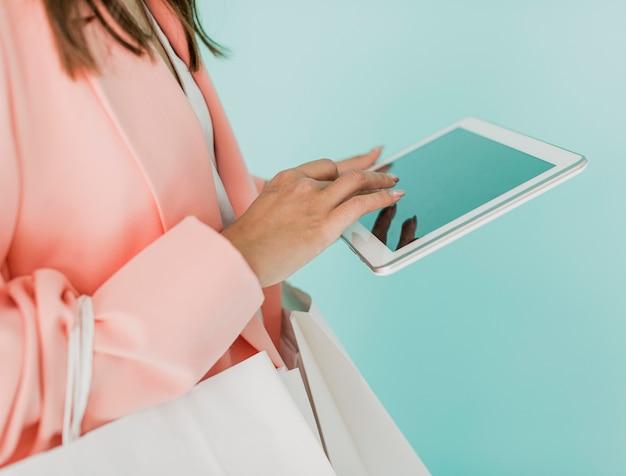 タブレットと買い物袋のブルネットの女性 無料写真