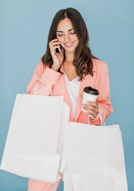 スマートフォンで話しているショッピングネットで幸せな女性 無料写真
