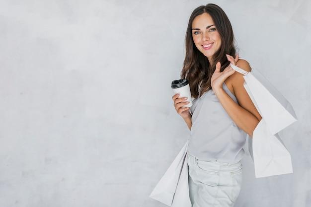 ショッピングネットとコーヒーとアンダーシャツのブルネットの女性 無料写真