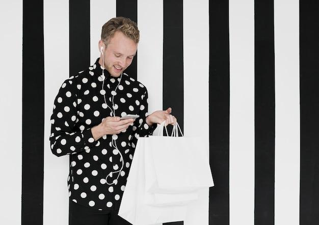 縞模様の背景に買い物袋を持つ男 無料写真