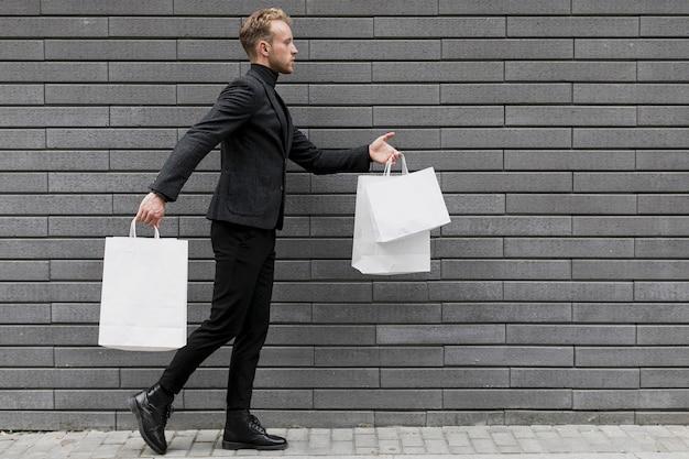 通りを歩いて買い物袋を持つ男 無料写真
