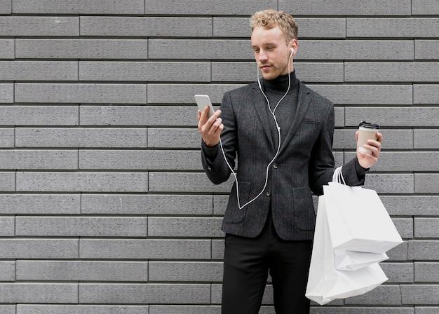 スマートフォンで笑顔の買い物袋を持つ孤独な男 無料写真