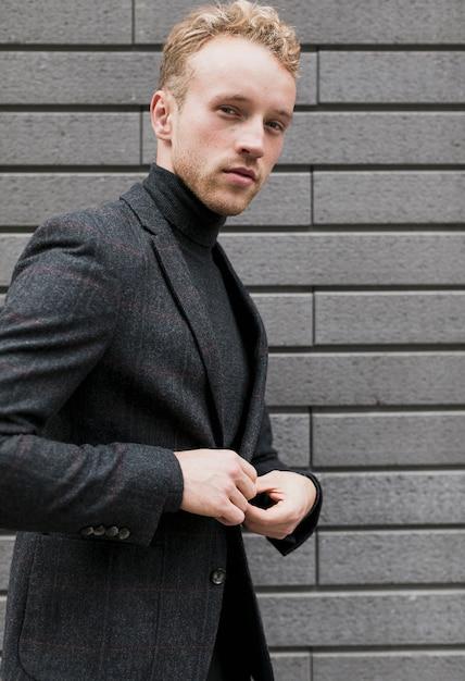 フォトジェニックな若い男が彼のジャケットを閉じる 無料写真