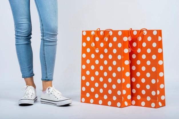 女性の足の近くのクローズアップショッピングバッグモックアップ 無料写真