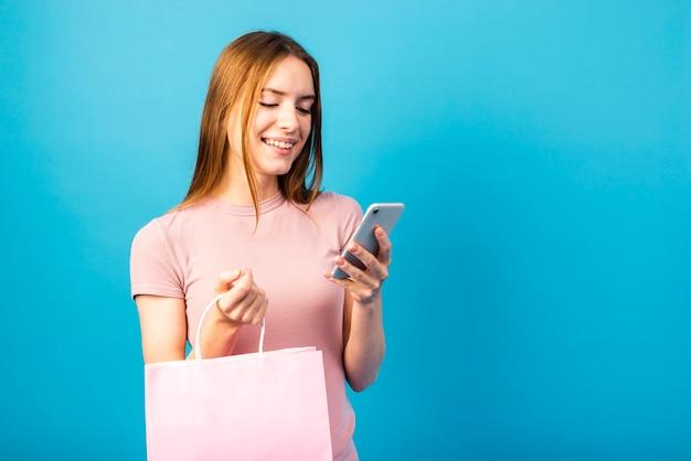 ミッドショット女性バッグを押しながら携帯電話を見て 無料写真