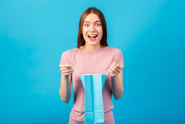Средний снимок портрет счастливой женщины, держащей сумку Бесплатные Фотографии