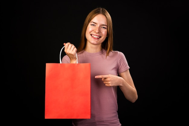 Вид спереди счастливой женщины, указывая на ее красная сумка Бесплатные Фотографии
