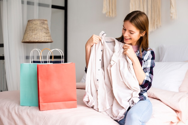 Женщина смотрит на рубашку и улыбается Бесплатные Фотографии