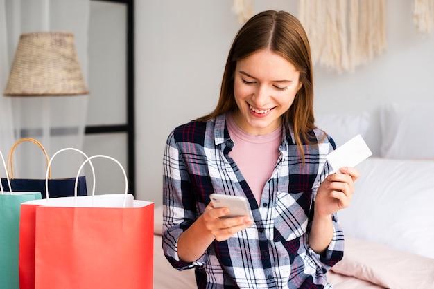 クレジットカードを使用してオンラインで商品を購入する女性 無料写真