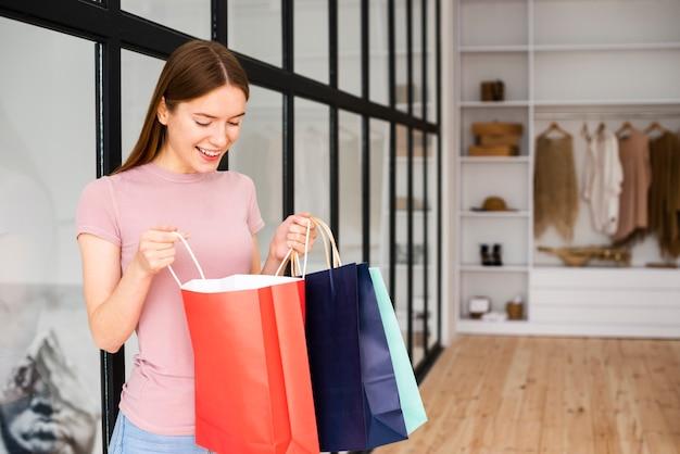 Женщина смотрит в бумажные пакеты Бесплатные Фотографии