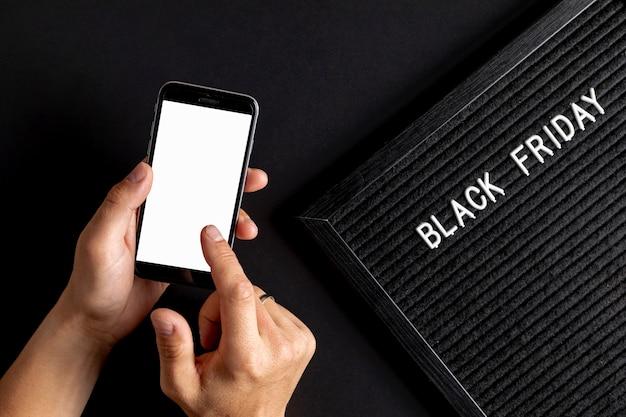 黒い金曜日のカーペットの横にモックアップ電話を使用して手 無料写真