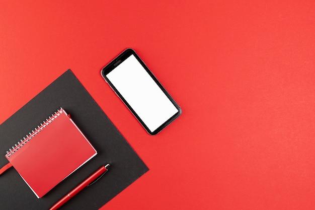 赤いノートブックの横にモックアップの電話 無料写真