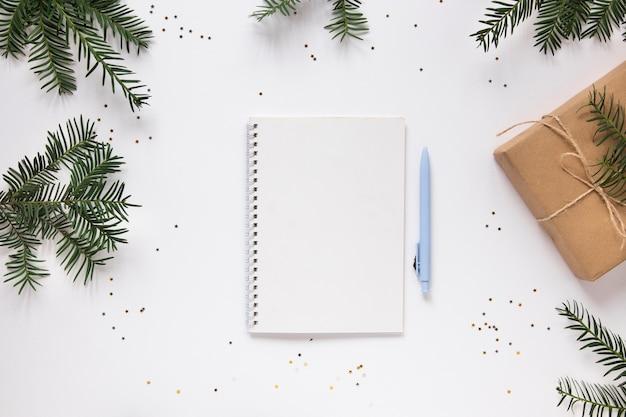 松の枝を持つノートブックモックアップ 無料写真