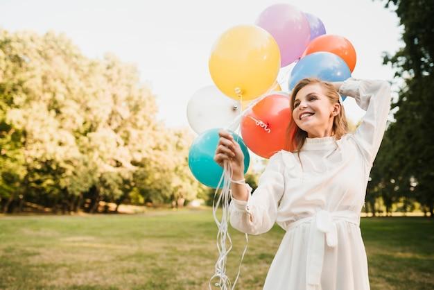 Улыбающаяся девушка в парке держит воздушные шары Бесплатные Фотографии