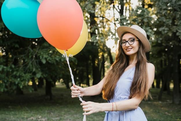 Улыбающаяся девушка с воздушными шарами смотрит в камеру Бесплатные Фотографии