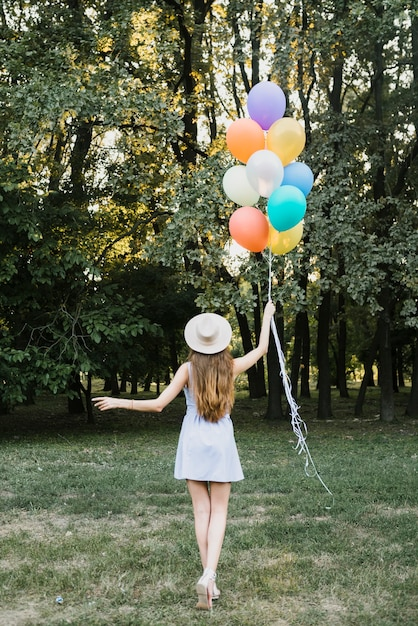 Вид спереди женщина с шарами ходьбе Бесплатные Фотографии