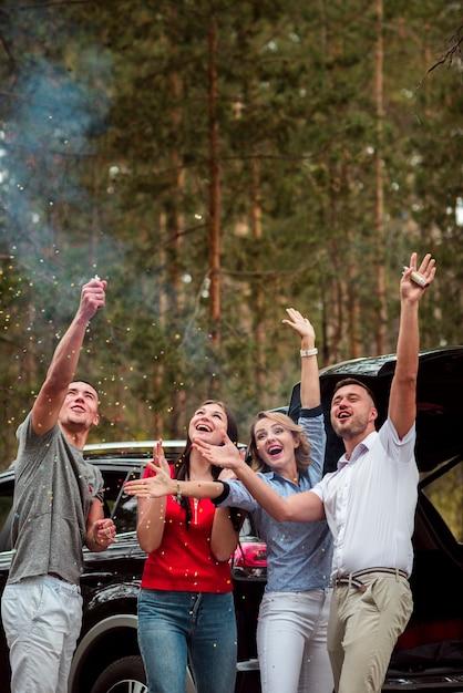 Восторженные друзья празднуют на свежем воздухе Бесплатные Фотографии