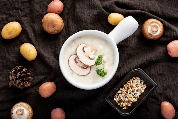 黒い布の上のキノコと白い瓶にキノコのスープ 無料写真