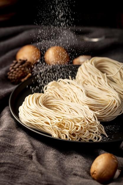 きのこと灰色の背景に黒のプレートの麺 無料写真