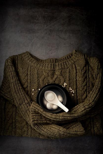灰色の背景に緑のセーターにスープと黒のボウル 無料写真