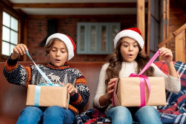 Средний снимок удивил брата и сестру открытием подарков Бесплатные Фотографии