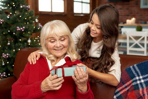 おばあちゃんに贈り物を提供するミディアムショットの孫娘 無料写真