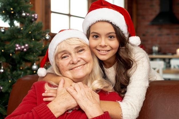 Средний снимок счастливая девушка обнимает бабушку Бесплатные Фотографии