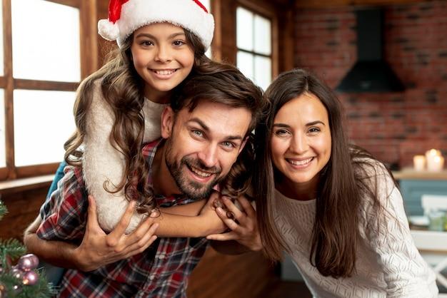 ミディアムショットの幸せな親と屋内でポーズの女の子 無料写真