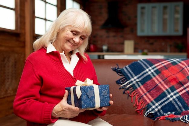 Средний снимок счастливая бабушка держит подарок Бесплатные Фотографии