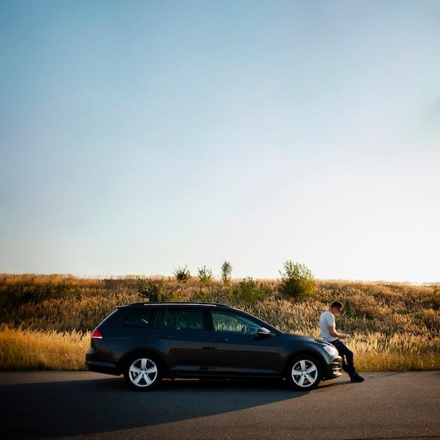 Человек сидит на капоте автомобиля Бесплатные Фотографии