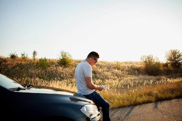 車のボンネットで休む若い男 無料写真