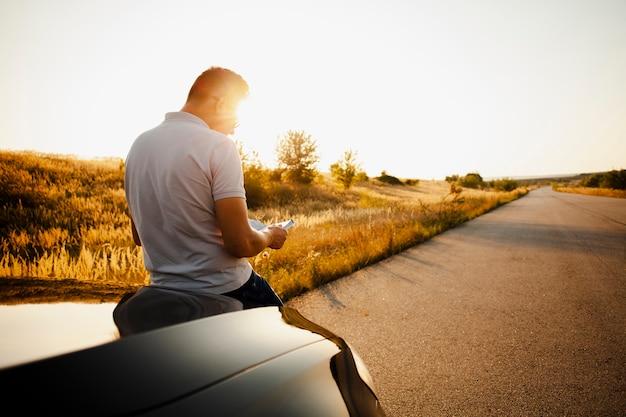 車のボンネットの上に座って本を読んでいる人 無料写真