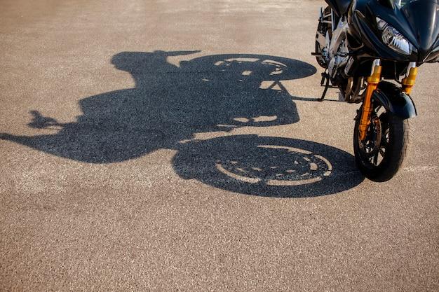 Тень оранжевого мотоцикла на асфальте Бесплатные Фотографии