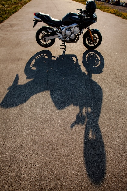 太陽の下でバイクの影 無料写真