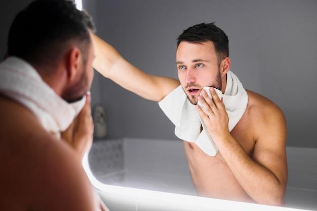バスルームの鏡で見ている若い男 無料写真