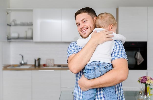 陽気な若い男が子供を抱いて 無料写真
